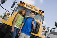 Stock Photo of Teenagers By School Bus