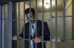 Businessman Standing Behind Bars Stock Photos