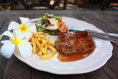 pork steak with vegetables and gravy - stock photo