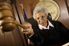 Judge Pointing Gavel In Courtroom Stock Photos