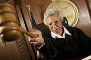Stock Photo of Judge Pointing Gavel In Courtroom