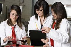 Professor Assisting Students In Chemistry Lab - stock photo