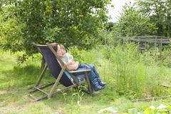 Mother And Son Sitting On Deck Chair In Allotment - stock photo
