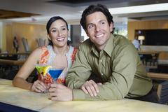 Couple Drinking Martinis At A Bar - stock photo