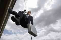 Spy Rappelling with Suitcase - stock photo