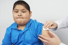 Disinfecting boy's arm Stock Photos