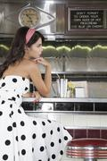 Young Woman Sitting At Diner Counter - stock photo