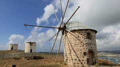 old windmill with white clouds and blue sky - stock footage