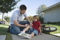 Stock Photo of Father Putting Plaster On Son's Knee Outdoors