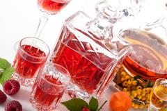 Rapsberry and rowanberry liqueurs Stock Photos