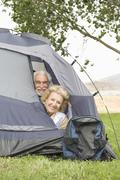 Senior Couple With Heads At Tent Flap - stock photo