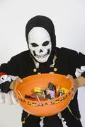 Boy In Halloween Outfit Holding Bowl Of Candies - stock photo
