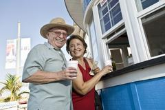 Senior Couple Buying Drinks At Food Stand - stock photo