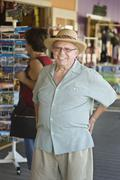 Vanhempi mies seisoi matkamuisto stand - stock photo