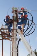 Electricians troubleshoot on power lines Stock Photos