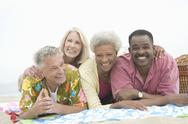 Multiethnic Friends Lying Down On Stomach At Beach Stock Photos