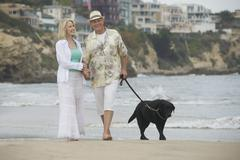 Senior Couple Walking With Dog At Beach - stock photo