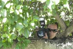 Paparazzi Photographer Behind Tree - stock photo