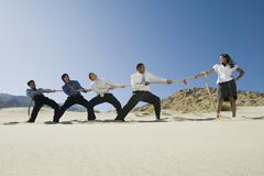 Businessmen Playing Tug Of War Against One Woman - stock photo