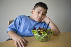 Stock Photo of Unhappy preadolescent Boy Sitting At Desk With Salad