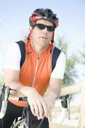 Male cyclist leaning on handlebars Stock Photos
