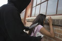 Hooded Man Robbing Young Woman With Knife - stock photo