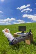 Businessman relaxing feet up desk in green field Stock Photos