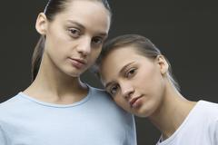 Stock Photo of Contemplative Sisters Against Black Background