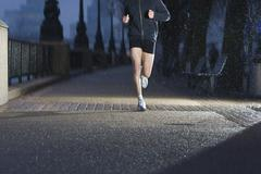 Man Jogging On City Pavement At Dawn - stock photo