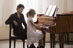 Girl And Teacher Playing Piano Stock Photos