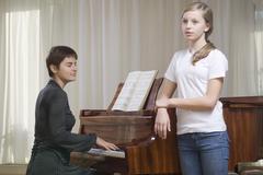 Girl Singing As Teacher Play The Piano Stock Photos