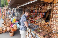 novgorod - august 10: young woman choose russian handmade souvenirs at the gi - stock photo