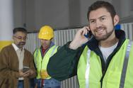 Man On Call With Colleagues In Factory Stock Photos
