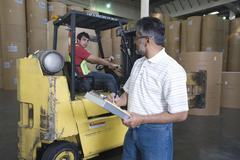 Man With Colleague In Forklift Track At Factory Stock Photos