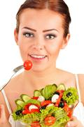young woman eating vegetable salad - stock photo