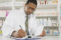 Male Pharmacist Working In Pharmacy - stock photo