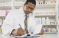 Stock Photo of Male Pharmacist Working In Pharmacy