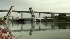 Freighter passing through open liftbridge Stock Footage