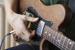 Man Strums Chord On Guitar - stock photo
