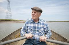 Elderly Man Rowing Boat Stock Photos