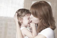 Stock Photo of Mother Comforts Crying Baby Girl