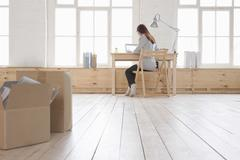 Woman Using Laptop At Desk In Loft Apartment - stock photo