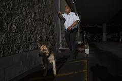 Security Guard In Alleyway Pursuit With Dog - stock photo