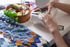 Woman Making Patchwork At Sewing Machine - stock photo