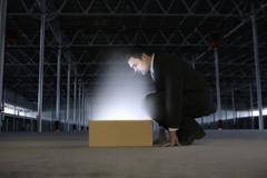 Businessman Looking At Glowing Box In Empty Warehouse Stock Photos