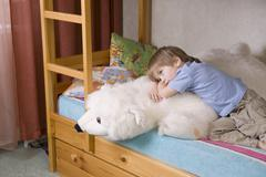 Stock Photo of Thoughtful Boy With Soft Toy Lying On Bunk Bed
