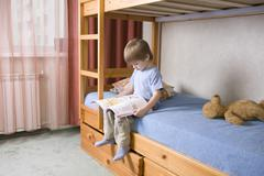 Stock Photo of Boy Reading Book On Bunk Bed