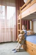 Bored Boy With Teddy Bear Leaning On Bunk Bed Stock Photos