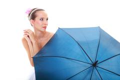 Wedding at raining day. Young bride in white dress with blue umbrella isolated. Stock Photos