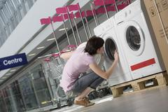 Stock Photo of Woman Examining Front Loader Of Washing Machine